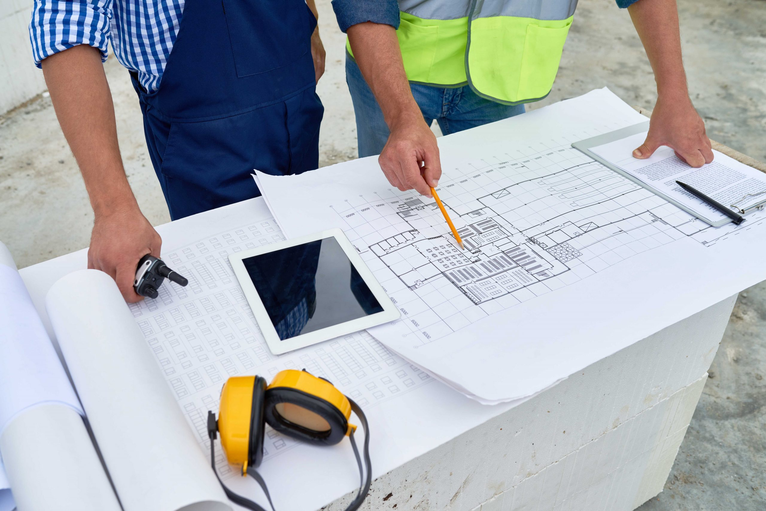 A project manager and construction worker looking over building plans.