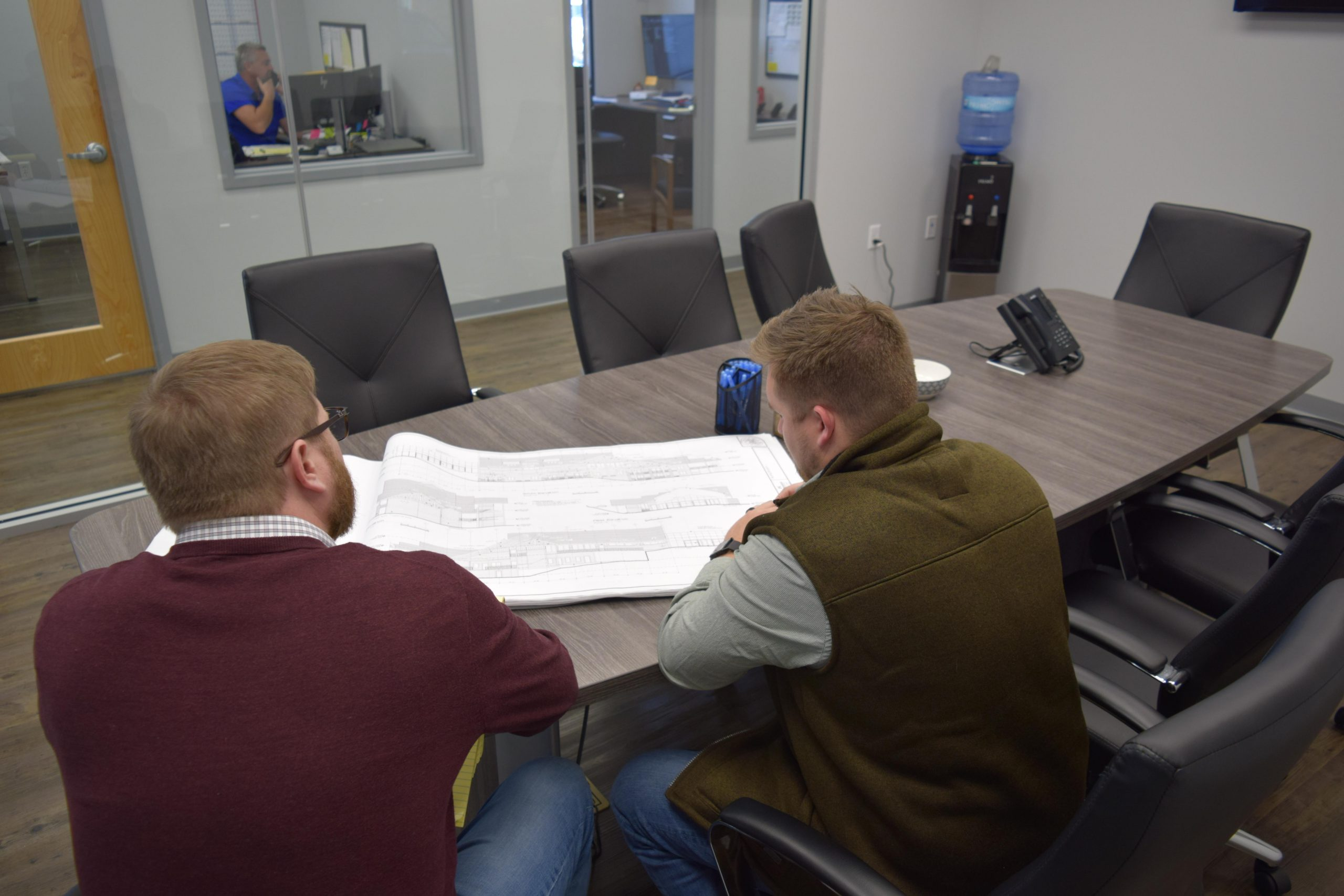 two general contractors sitting down discussing plans.